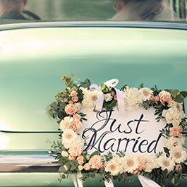 bride and groom leaving in a classic car